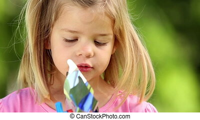 Little girl playing with pinwheel in the park on a sunny day...