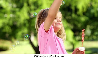 Little girl playing with bubbles in the park - Little girl...