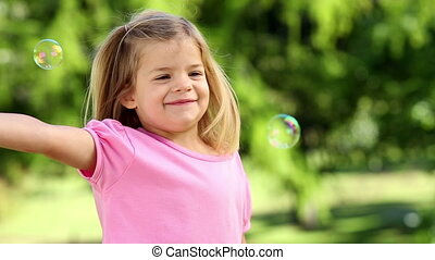 Little girl playing with bubbles in the park on a sunny day