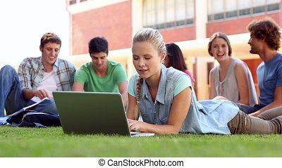 Blonde student using laptop with classmates sitting behind...
