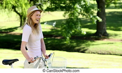 Pretty girl on a bike ride in the park on a sunny day
