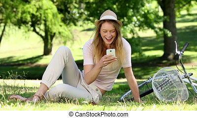 Pretty girl using smartphone beside her bike in the park on...
