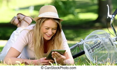 Pretty girl using tablet pc beside her bike in the park on a...