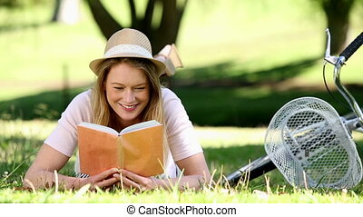 Pretty girl reading beside her bike in the park on a sunny...