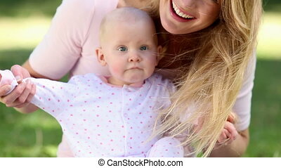Happy mother holding her baby girl in the park on a sunny...