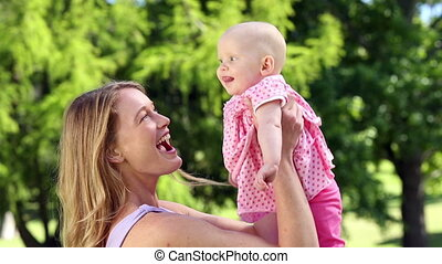 Happy mother playing with her baby girl in the park on a...