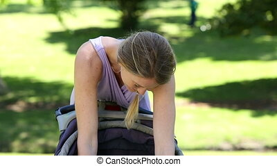 Mother tending to her baby girl in her pram in the park on a...