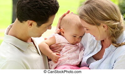 Happy parents with their baby girl in the park on a sunny...