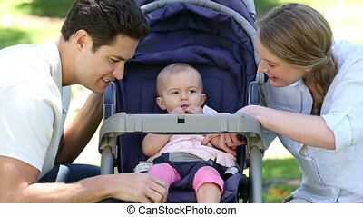 Happy parents tending to baby girl in pram in the park on a...