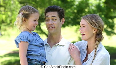 Happy parents with their little girl in the park on a sunny...