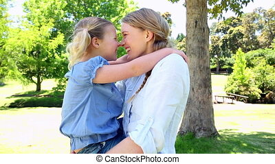 Happy mother holding her little girl in the park on a sunny...