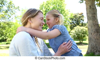 Happy little girl telling her mother a secret in the park on...