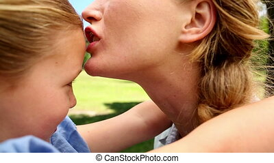 Happy mother kissing her little girl - Happy mother kissing...