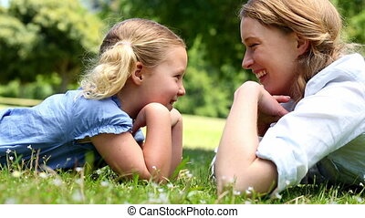 Happy mother lying on the grass with daughter