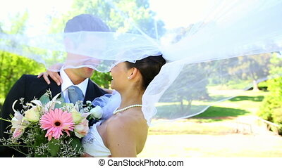 Happy newlyweds standing in the park on a sunny day