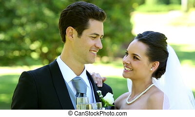 Happy newlyweds toasting with champagne on a sunny day