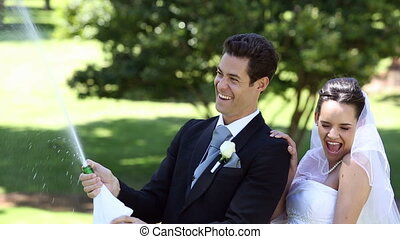 Happy newlyweds spraying bottle of champagne on a sunny day