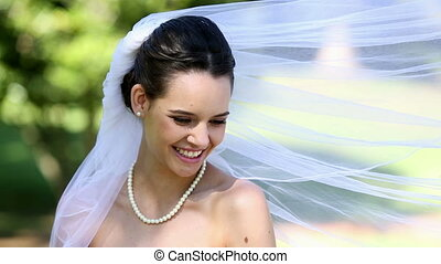 Beautiful bride smiling at camera in the park on a sunny day