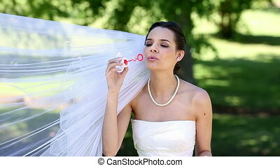 Beautiful bride blowing bubbles in the park on a sunny day