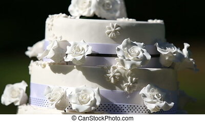 Wedding cake with cake toppers on a sunny day