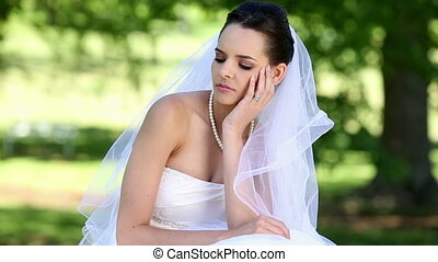 Upset bride sitting on the grass on a sunny day