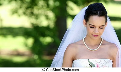 Beautiful bride smiling at camera in the park on a sunny day...