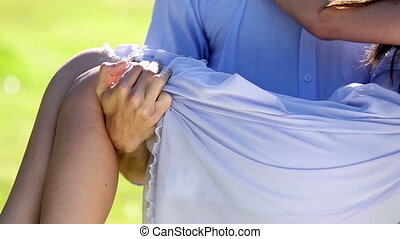 Man carrying his pretty girlfriend in the park on a sunny...