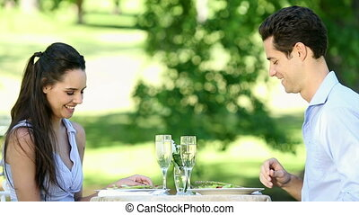 Couple having a romantic meal together outside on a sunny...
