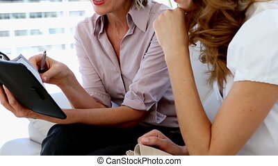 Businesswomen planning together on the sofa at home