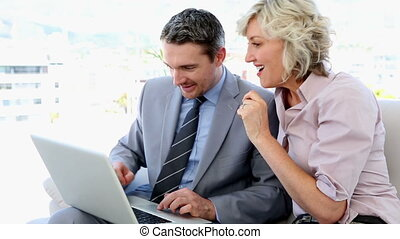 Business people working together on laptop sitting on sofa