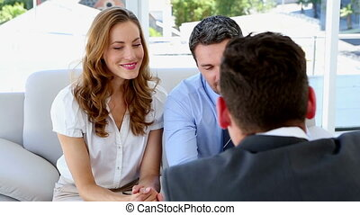 Couple talking to their financial advisor at home on couch