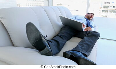 Businessman sleeping on couch with - Businessman sleeping on...