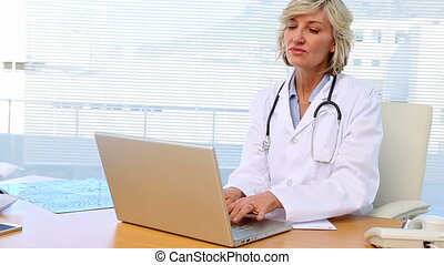 Blonde doctor working at her desk in office at the hospital