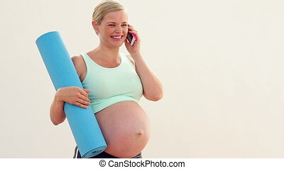 Pregnant blonde talking on the phone in a fitness studio