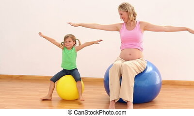 Blonde pregnant woman sitting on exercise ball with her...