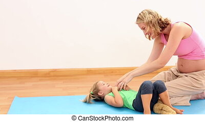 Blonde pregnant woman tickling her daughter