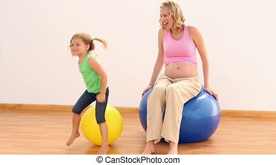 Blonde pregnant woman sitting on exercise ball - Blonde...