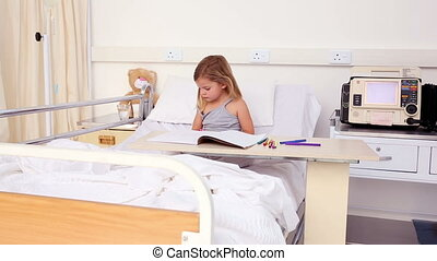 Little girl sitting in hospital bed colouring in the...