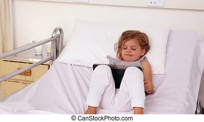 Little girl lying in hospital bed using a tablet in the...