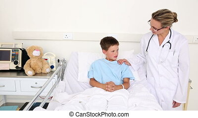 Little sick boy sitting in bed talking with doctor in the...