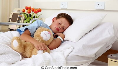 Little sick boy sleeping in bed with teddy bear in the...