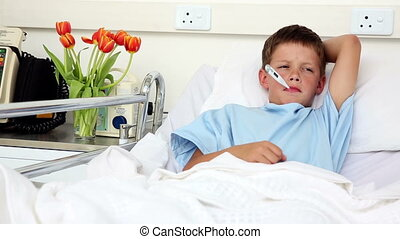 Little sick boy sitting in bed with thermometer