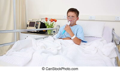 Little sick boy sitting in bed with oxygen mask in the...