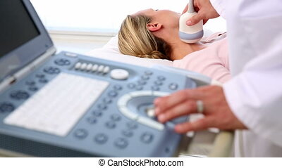 Doctor taking a sonogram of patients neck in the hospital