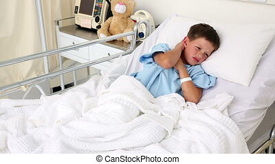 Little sick boy sitting in bed holding his neck in the...