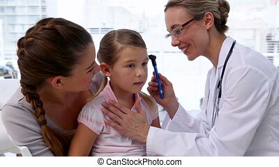 Doctor checking little girls ears in her office at the...