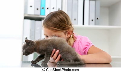 Little girl stroking a grey kitten at the vets