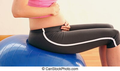 Pregnant blonde sitting on exercise ball in a fitness studio