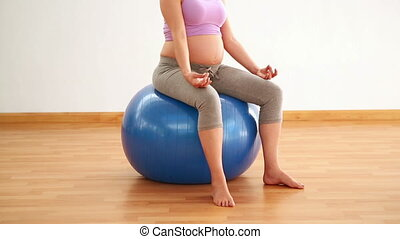 Pregnant brunette meditating on exercise ball in a fitness...
