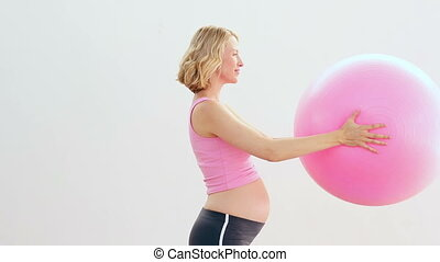 Pregnant blonde holding exercise ball in a fitness studio
